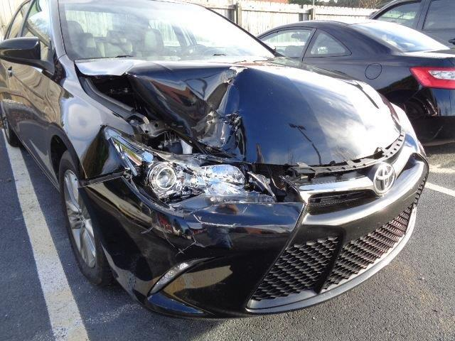 A Black Toyota Camry showing passenger-side front damage to the bumper, headlight and hood/engine.