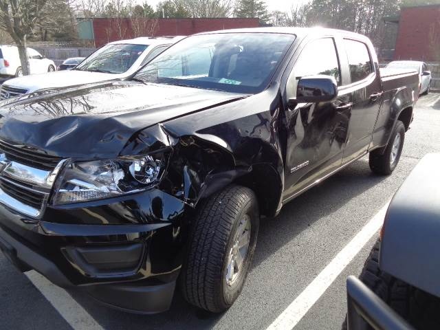 A Chevy Colorado Truck showing extensive damage to the side and front before the repair at the auto-body shop.