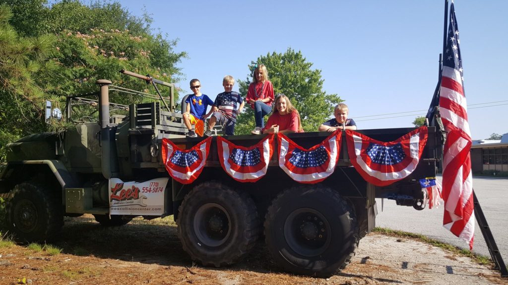 Children in a military truck decorated with American flags ready for the parade