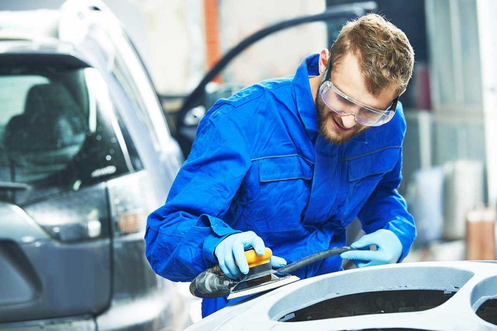 Paint Technician refinishing a car panel
