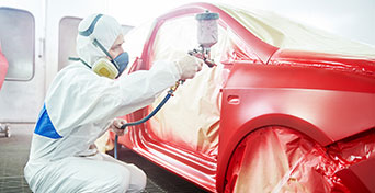 Technician using precision tools to paint car