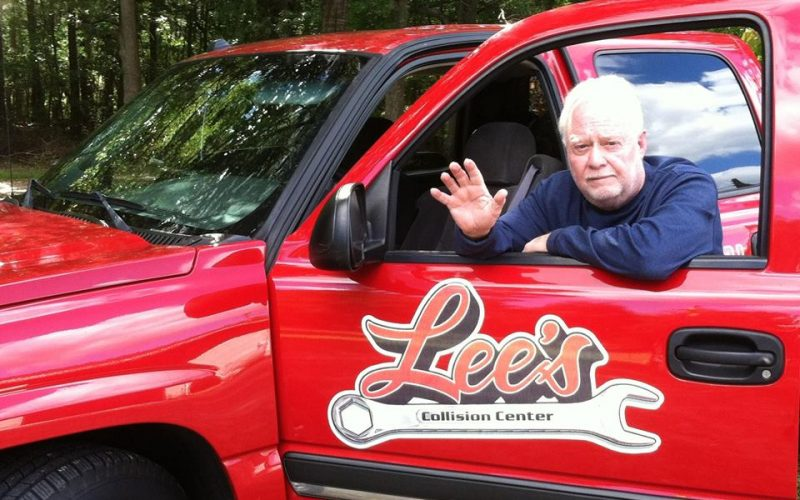 founder of Lee's Collision Center standing by his shiny red, branded truck